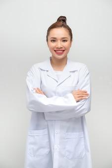 Médica sorridente, vestindo um jaleco com os braços cruzados contra a parede branca