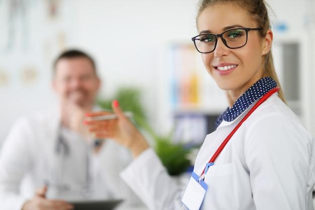 Médica sorrindo com colega junto closeup
