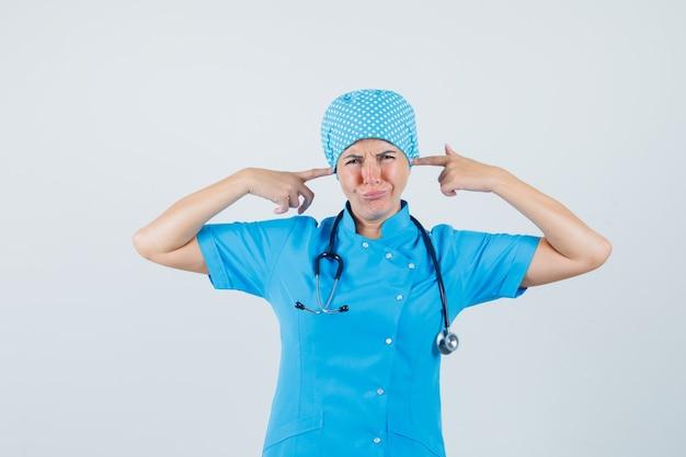 Médica tampando as orelhas com os dedos em uniforme azul e parecendo irritada. vista frontal.