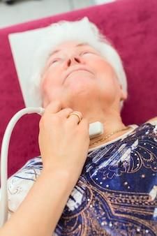 Médica testando tireoide de paciente sênior com dispositivo ultrassônico de cirurgia