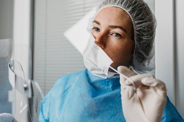 Médica tirando a máscara facial
