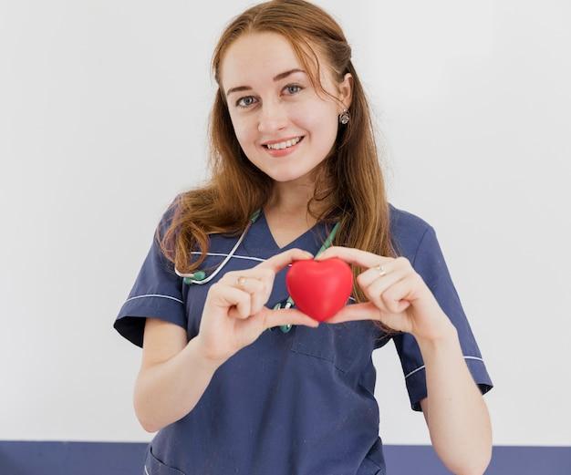 Médica tiro smiley médico segurando o brinquedo em forma de coração