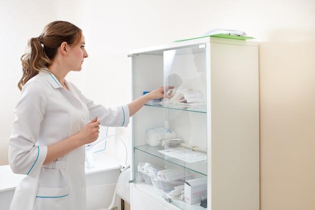 Médica tomando remédio da prateleira do consultório médico