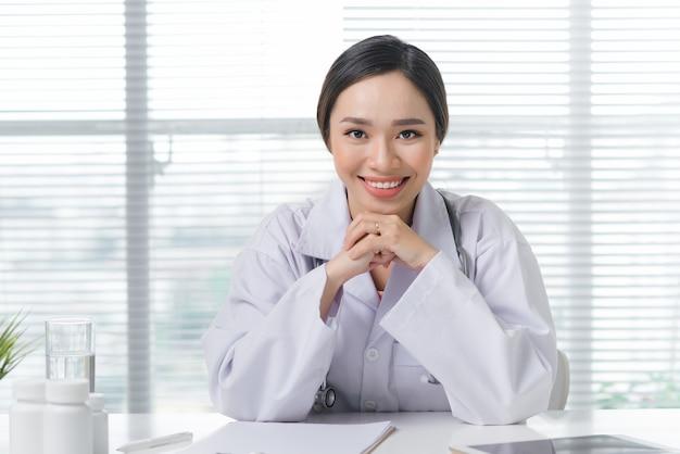 Médica trabalhando na mesa do escritório e sorrindo