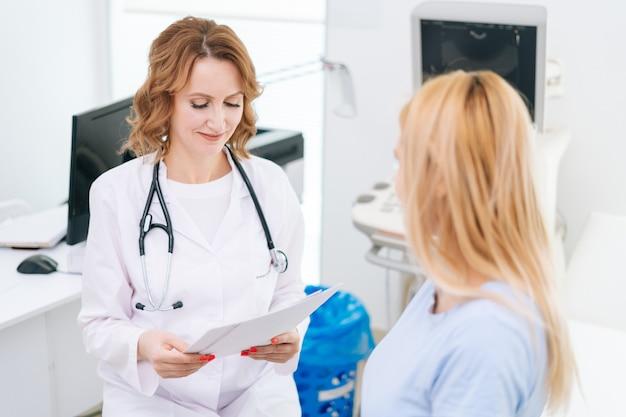 Médica transmite à jovem grávida de cabelos loiros os resultados e relatórios