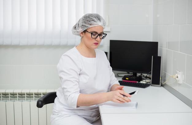 Médica usando óculos e um terno médico branco sentada em uma mesa com um telefone e um notebook no escritório da clínica