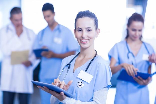 Médica usando tablet e sorrindo enquanto seus colegas de pé