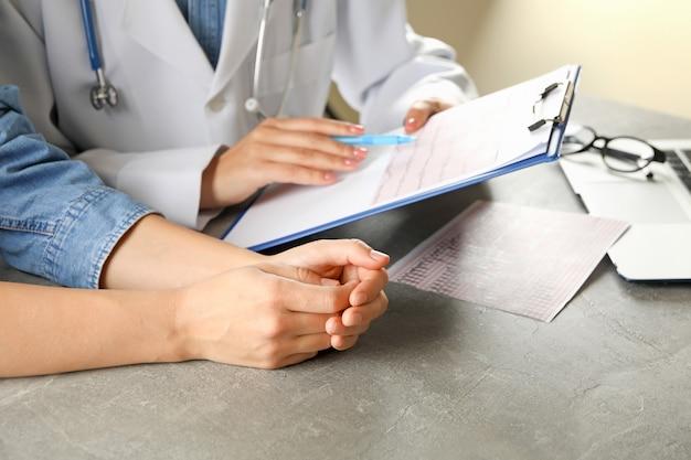 Médica verificando os resultados do eletrocardiograma com o paciente