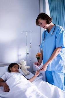 Médica, verificando um nível de açúcar do paciente
