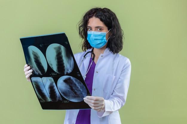 Médica vestindo jaleco branco com estetoscópio e máscara protetora médica em pé com raio-x de pulmões com cara séria em verde isolado