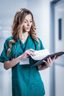 Médica vestindo jaleco branco com estetoscópio e suporte de papel azul nas mãos, isolado no fundo branco