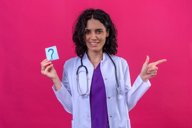 Médica vestindo jaleco branco com estetoscópio segurando um papel lembrete com ponto de interrogação muito feliz apontando com o dedo para o lado em rosa isolado