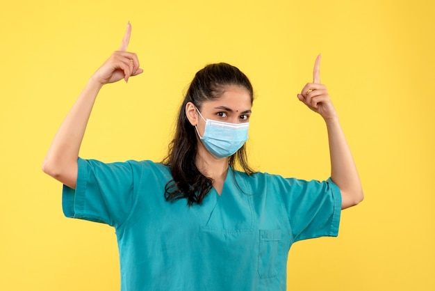 Médica vista frontal apontando com o dedo em pé no teto
