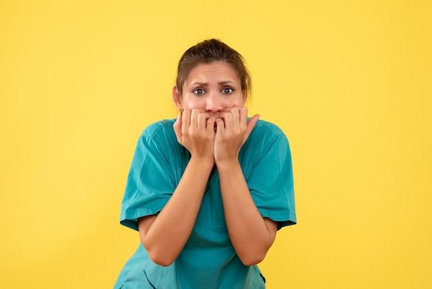 Médica vista frontal com camisa médica assustada e nervosa em um fundo amarelo