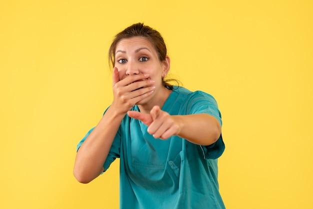 Médica vista frontal com camisa médica no fundo amarelo