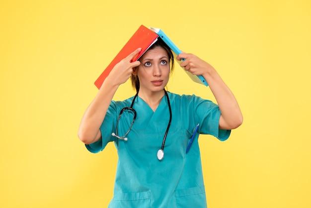 Médica vista frontal com camisa médica segurando anotações sobre fundo amarelo