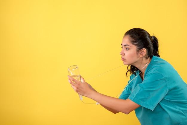 Médica vista frontal com frasco de soro em pé