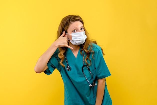 Médica vista frontal com máscara em um espaço amarelo