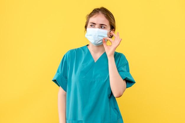Médica vista frontal com máscara estéril em fundo amarelo covidemia de saúde hospitalar