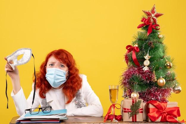Médica vista frontal com máscara estéril segurando máscara de festa perto de presentes de natal