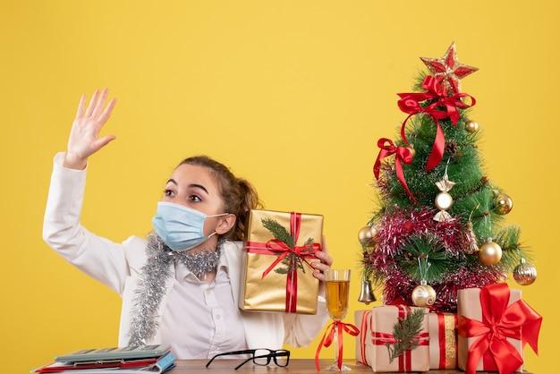 Médica vista frontal com máscara segurando um presente acenando
