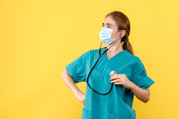 Médica vista frontal com máscara sobre fundo amarelo vírus da saúde pandêmico covid