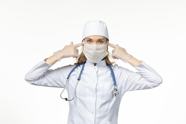 Médica vista frontal com traje médico usando máscara e luvas devido a coronavírus na mesa de luz covidêmica - doença por vírus de doença pandêmica