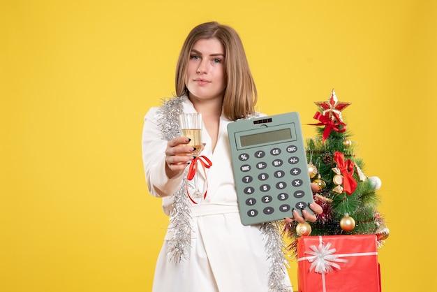 Médica vista frontal em pé e segurando uma calculadora em um fundo amarelo com uma árvore de natal e caixas de presente