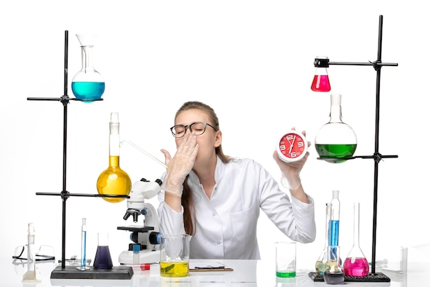 Médica vista frontal em terno médico branco segurando relógios e bocejando sobre fundo branco vírus covid pandemia de química