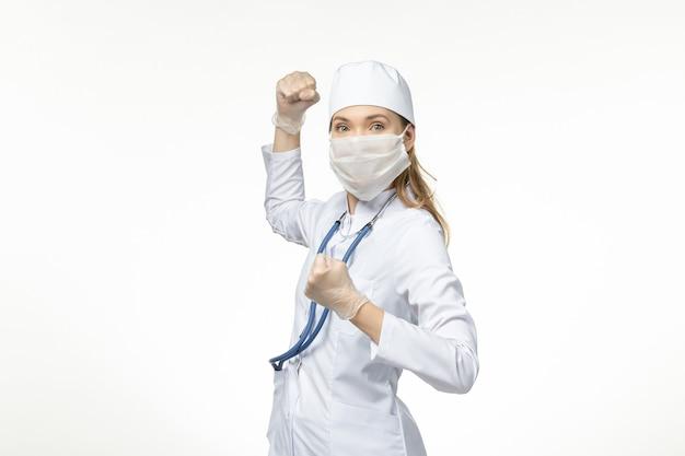 Médica vista frontal em traje médico branco e máscara como proteção contra coronavírus na doença de parede branca clara covid-doença pandêmica
