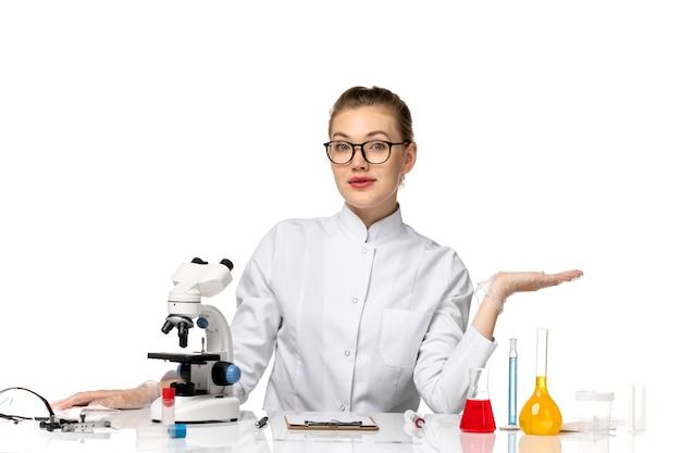 Médica vista frontal em traje médico branco, sentada em frente à mesa com soluções na mesa branca