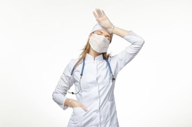 Médica vista frontal em traje médico com máscara e luvas devido a coronavírus em doença de parede branca clara, pandemia de saúde covidvírus