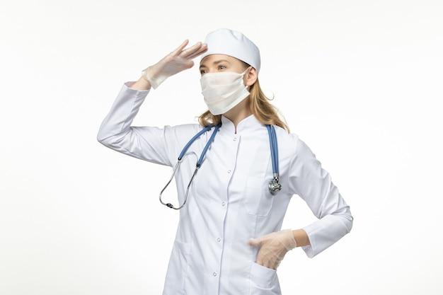 Médica vista frontal em traje médico usando máscara e luvas devido a coronavírus no vírus da covidose pandêmica de mesa branca