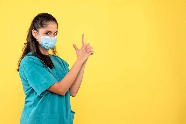 Médica vista frontal fazendo arma de dedo em pé