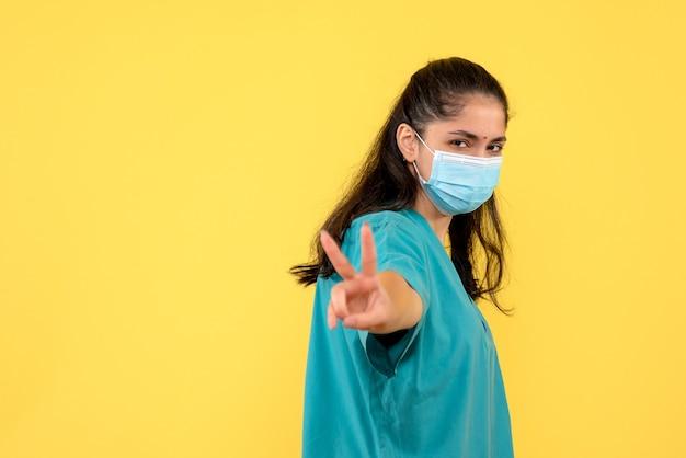 Médica vista frontal fazendo sinal de ok em pé