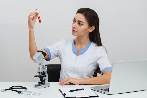 Médica vista frontal, olhando para uma amostra de sangue