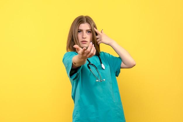Médica vista frontal parada no espaço amarelo