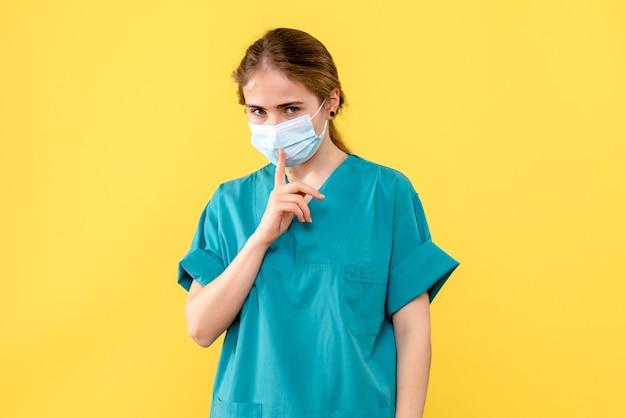 Médica vista frontal pedindo silêncio sobre fundo amarelo hospital de saúde covid-
