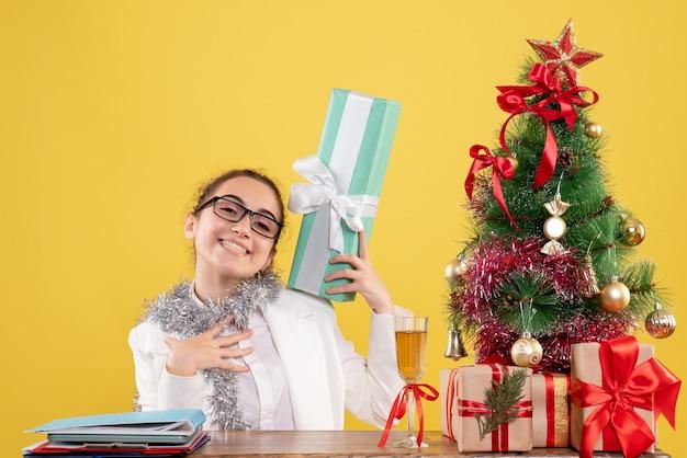Médica vista frontal sentada ao redor de presentes de natal e árvore segurando um presente em fundo amarelo