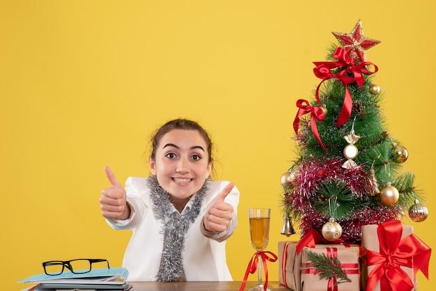 Médica vista frontal sentada ao redor de uma árvore e presentes de natal em fundo amarelo