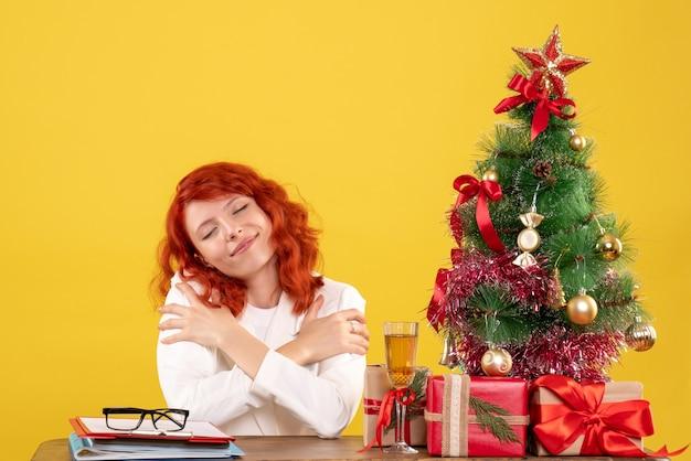 Médica vista frontal sentada atrás da mesa com presentes de natal em fundo amarelo com árvore de natal e caixas de presente