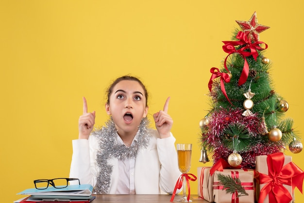 Médica vista frontal sentada atrás de sua mesa em fundo amarelo com árvore de natal e caixas de presente