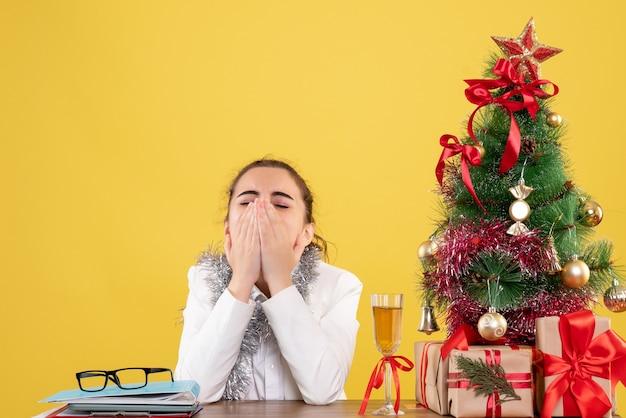 Médica vista frontal sentada atrás de uma mesa com presentes de natal e árvore bocejando sobre fundo amarelo