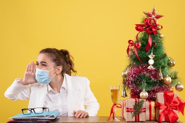 Médica vista frontal sentada com máscara estéril chamando fundo amarelo com árvore de natal e caixas de presente