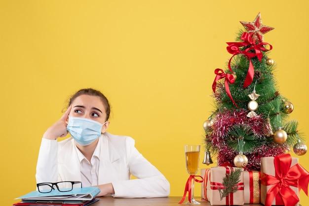 Médica vista frontal sentada com máscara estéril em fundo amarelo com árvore de natal e caixas de presente