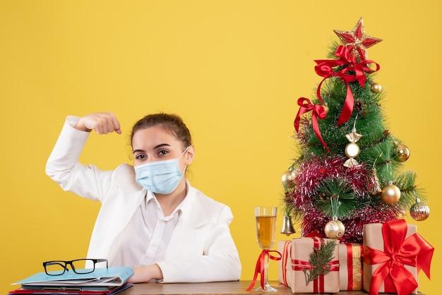 Médica vista frontal sentada com máscara estéril, flexionando sobre fundo amarelo com árvore de natal e caixas de presente