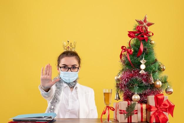 Médica vista frontal sentada com máscara estéril pedindo para parar em um fundo amarelo com árvore de natal e caixas de presente