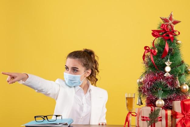 Médica vista frontal sentada com máscara protetora apontando sobre fundo amarelo