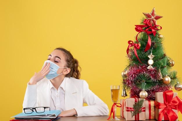 Médica vista frontal sentada com máscara protetora bocejando sobre fundo amarelo com árvore de natal e caixas de presente