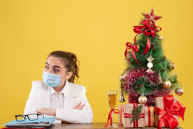 Médica vista frontal sentada com máscara protetora em fundo amarelo com árvore de natal e caixas de presente